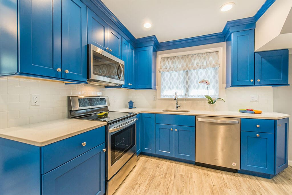 Blue kitchen remodel with stainless steel appliances, white subway tile backsplash, wood tile floor in Rockaway, New Jersey renovated by JMC Home Improvement Specialists
