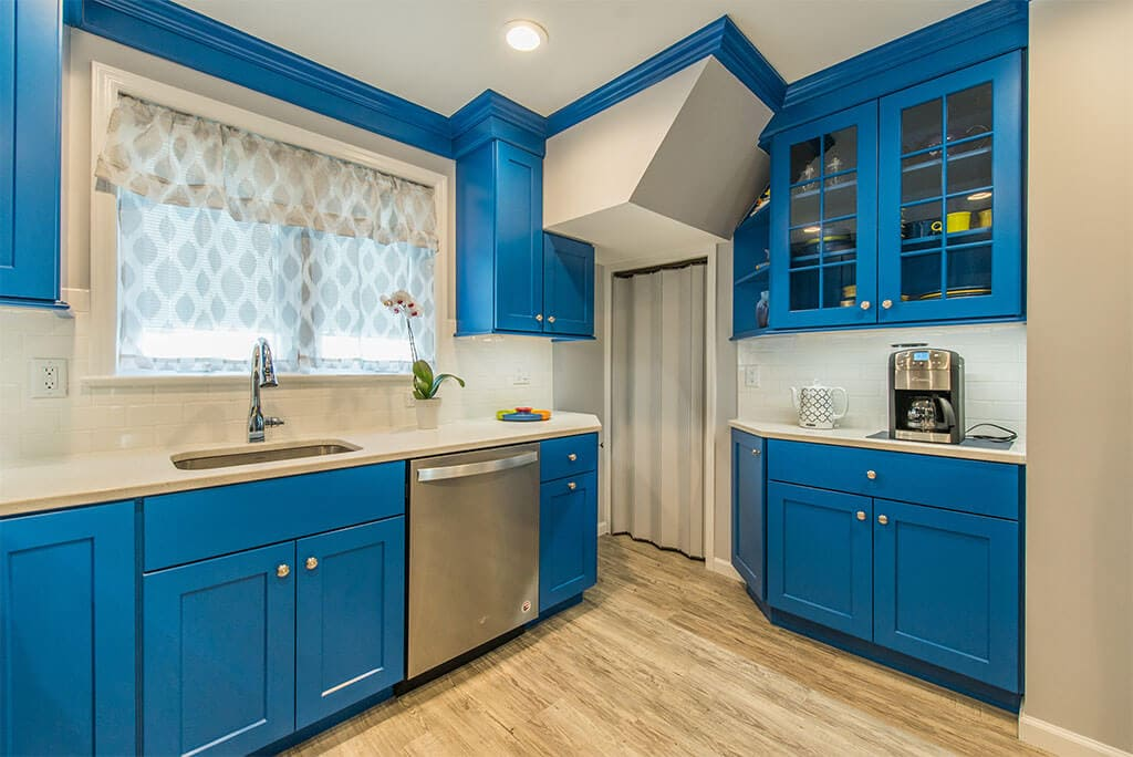 Blue cabinets in kitchen remodel with glass upper cabinets for display and open shelving, stainless steel appliances, quartz counters, white subway tile backsplash, wood tile floor in Rockaway, New Jersey renovated by JMC Home Improvement Specialists