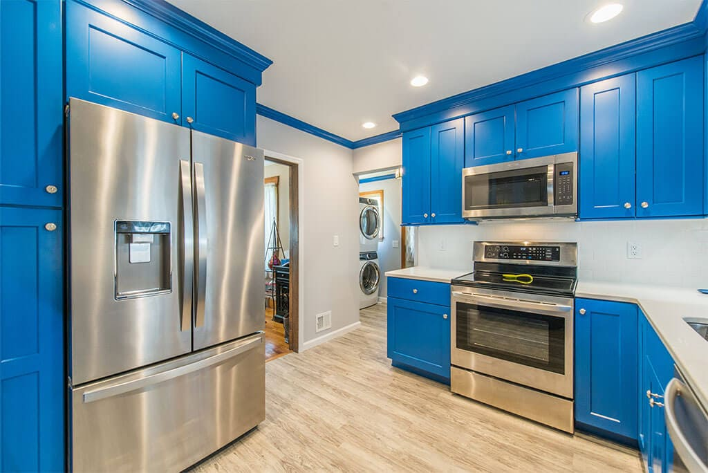 Blue kitchen remodel with stainless steel appliances, white subway tile backsplash, wood tile floor with attached laundry room in Rockaway, New Jersey renovated by JMC Home Improvement Specialists