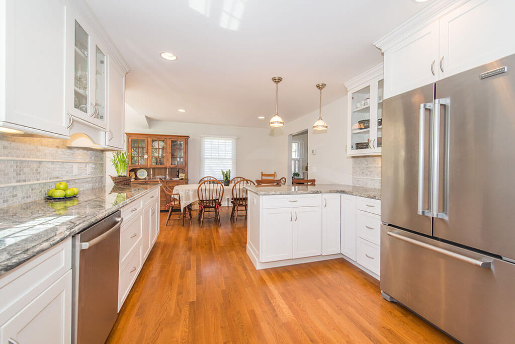 Open concept white kitchen remodel with white shaker cabinets, glass upper cabinet, granite countertops, pendant lighting, stainless appliances, dining area with hardwood flooring in Chatham, NJ renovated by JMC Home Improvement Specialists