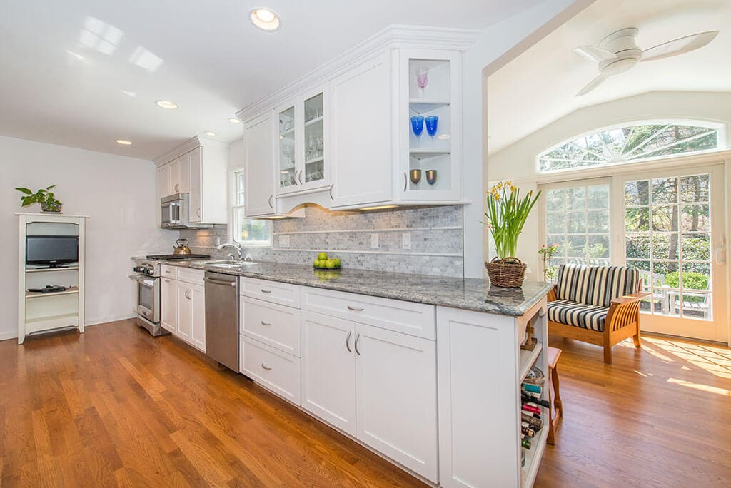 Open concept white kitchen remodel with white shaker cabinets, glass upper cabinet, granite countertops, vaulted ceilings in sunroom with transom windows and French doors and hardwood flooring in Chatham, NJ renovated by JMC Home Improvement Specialists