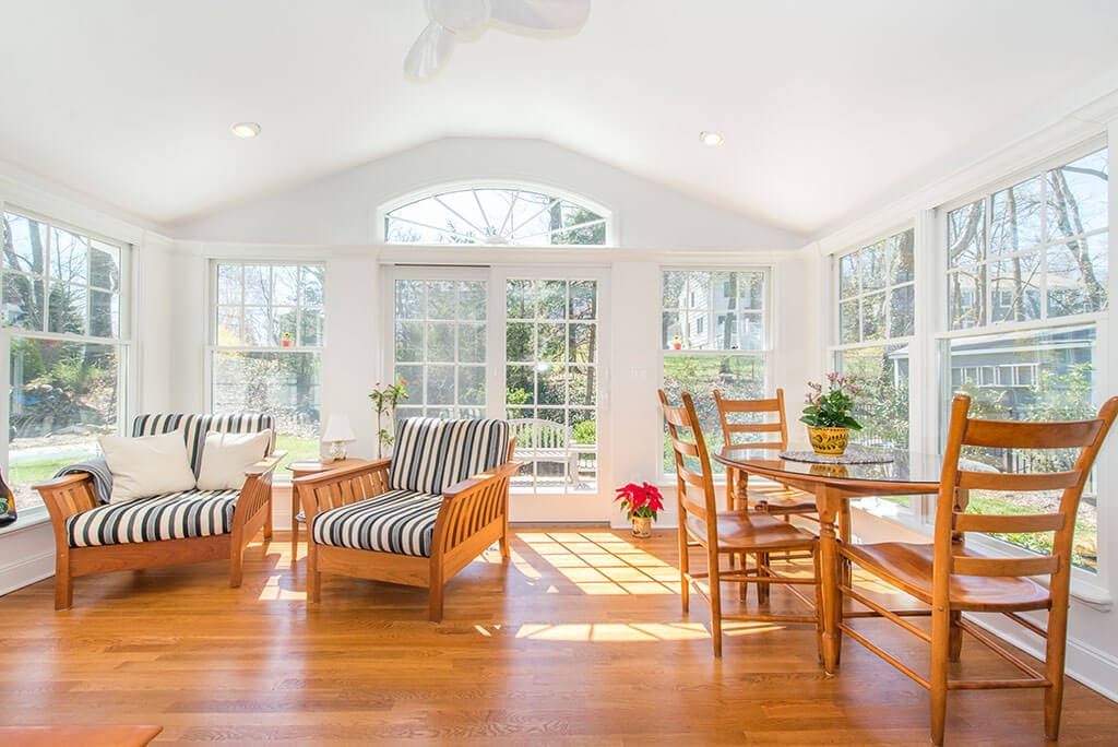 Sunroom with vaulted ceilings, ceiling fan, highhats, hardwood flooring and transom window over French doors in Chatham, NJ renovated by JMC Home Improvement Specialists