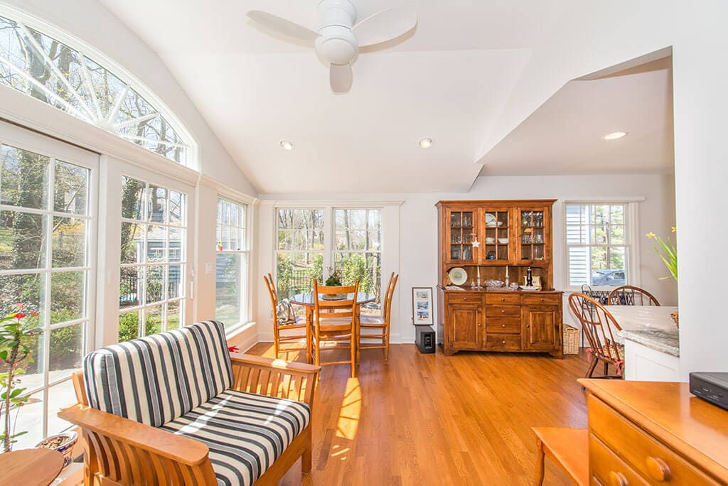 White sunroom with vaulted ceilings, ceiling fan, highhats, hardwood flooring and transom arch window over French doors in Chatham, NJ renovated by JMC Home Improvement Specialists