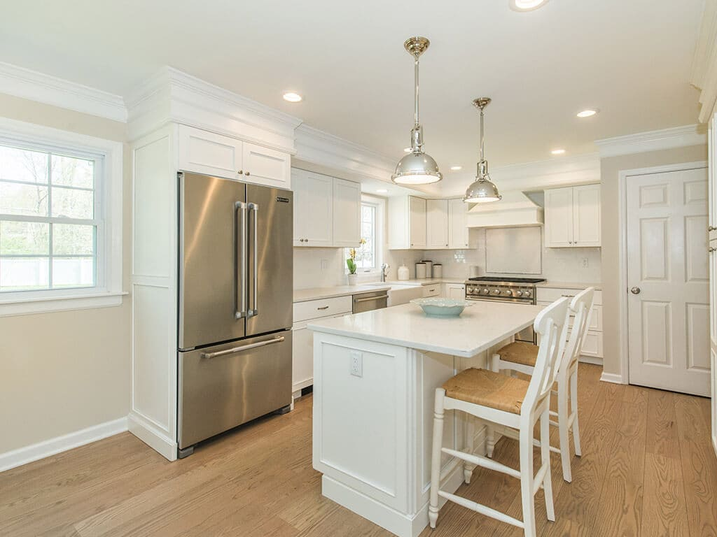 White kitchen remodel with shaker cabinets, quartz countertops, subway tile backsplash and hardwood flooring in Morris County, NJ renovated by JMC Home Improvement Specialists