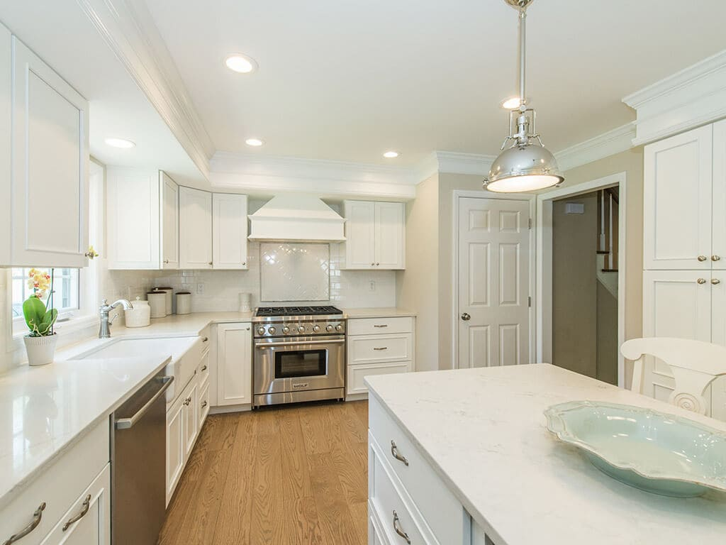 White kitchen remodel with shaker cabinets, quartz countertops, subway tile backsplash, custom wood hood, crown molding and hardwood flooring in Morris County, NJ renovated by JMC Home Improvement Specialists