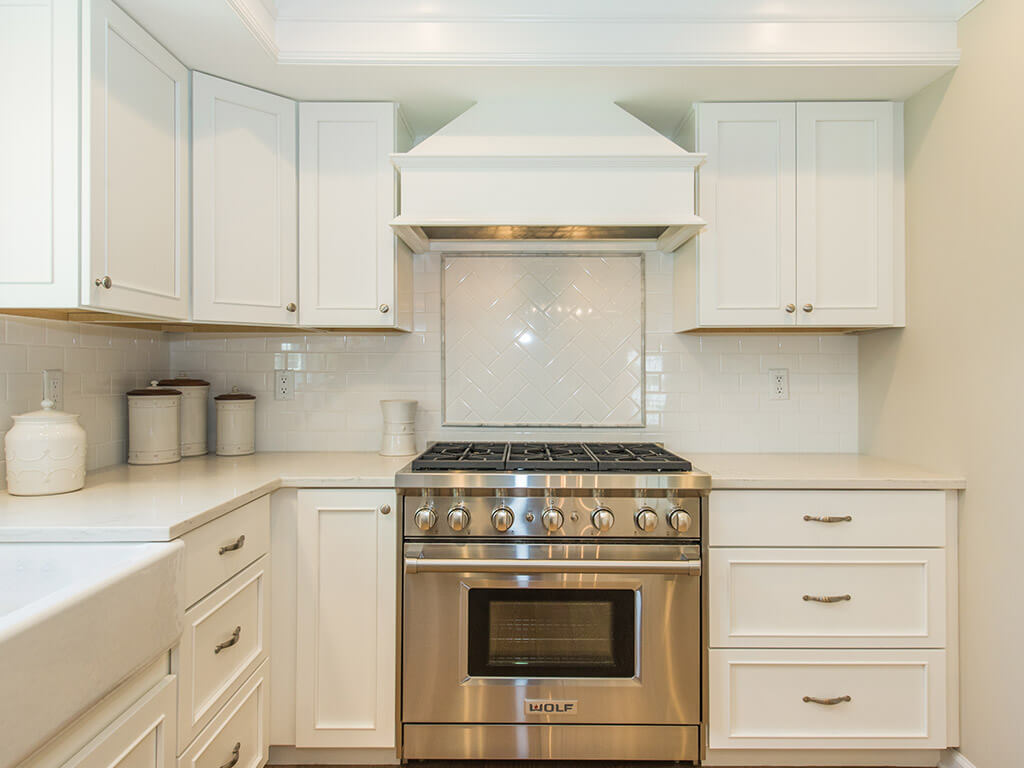 White kitchen remodel with shaker cabinets, quartz countertops, subway tile backsplash, custom wood hood, crown molding, apron sink and hardwood flooring in Morris County, NJ renovated by JMC Home Improvement Specialists