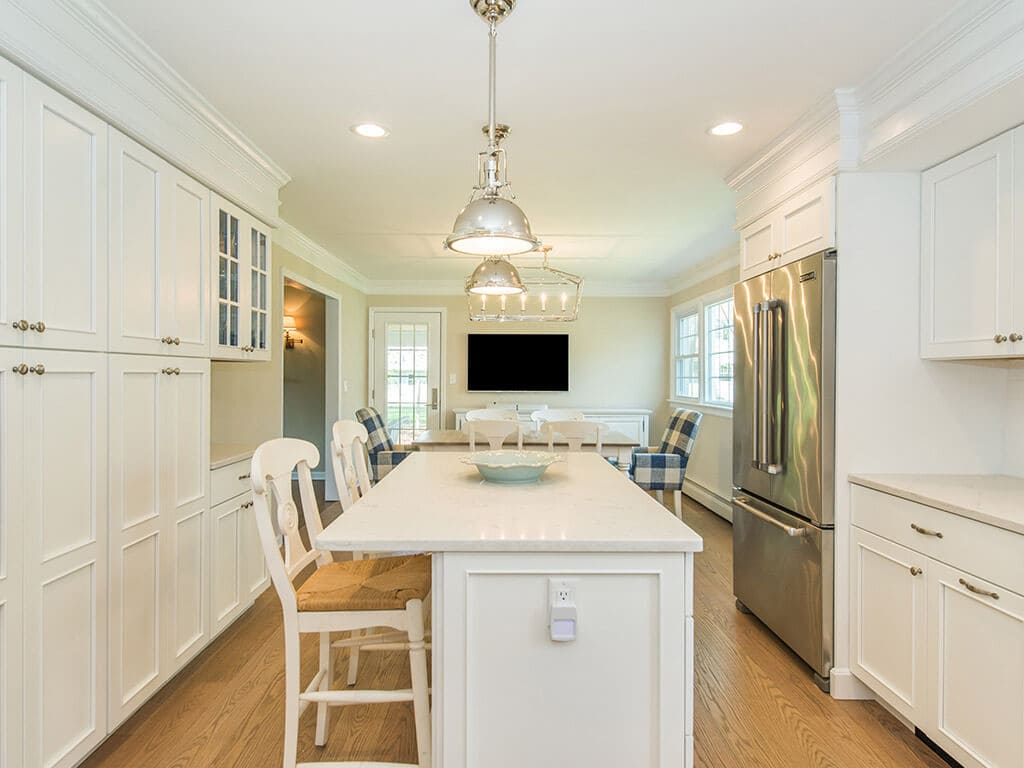 Open concept white kitchen remodel with cabinets, quartz countertops, subway tile backsplash, crown molding, apron sink, stainless appliances and hardwood flooring in Morris County, NJ renovated by JMC Home Improvement Specialists