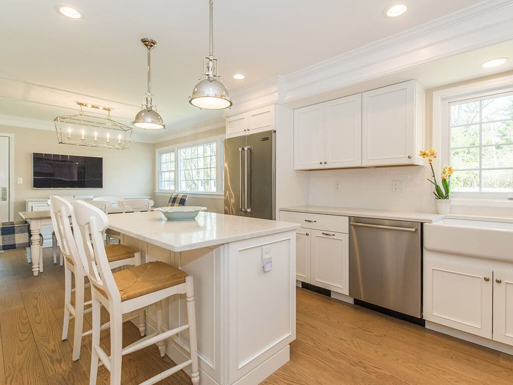 White kitchen remodel with cabinets, quartz countertops, subway tile backsplash, crown molding, apron sink, stainless appliances, wood hood and hardwood flooring in Morristown, NJ renovated by JMC Home Improvement Specialists