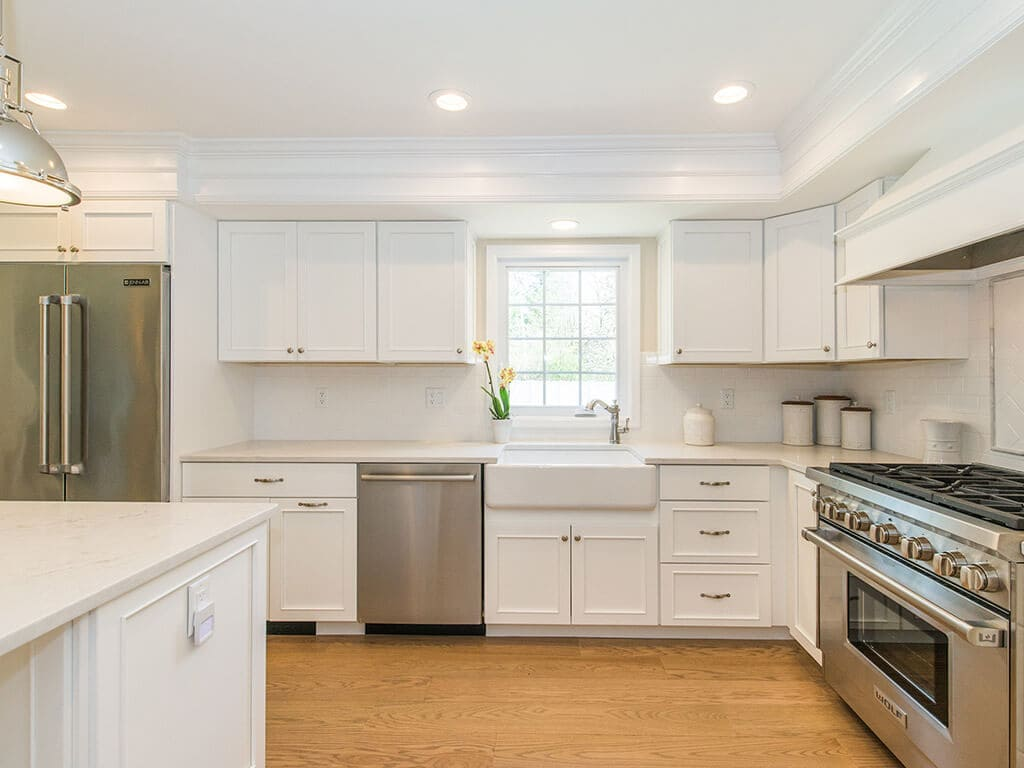 Open concept white kitchen remodel with white pantry cabinets, glass upper cabinet doors, quartz countertops, crown molding, pendant lighting over island and hardwood flooring in Morristown, NJ renovated by JMC Home Improvement Specialists