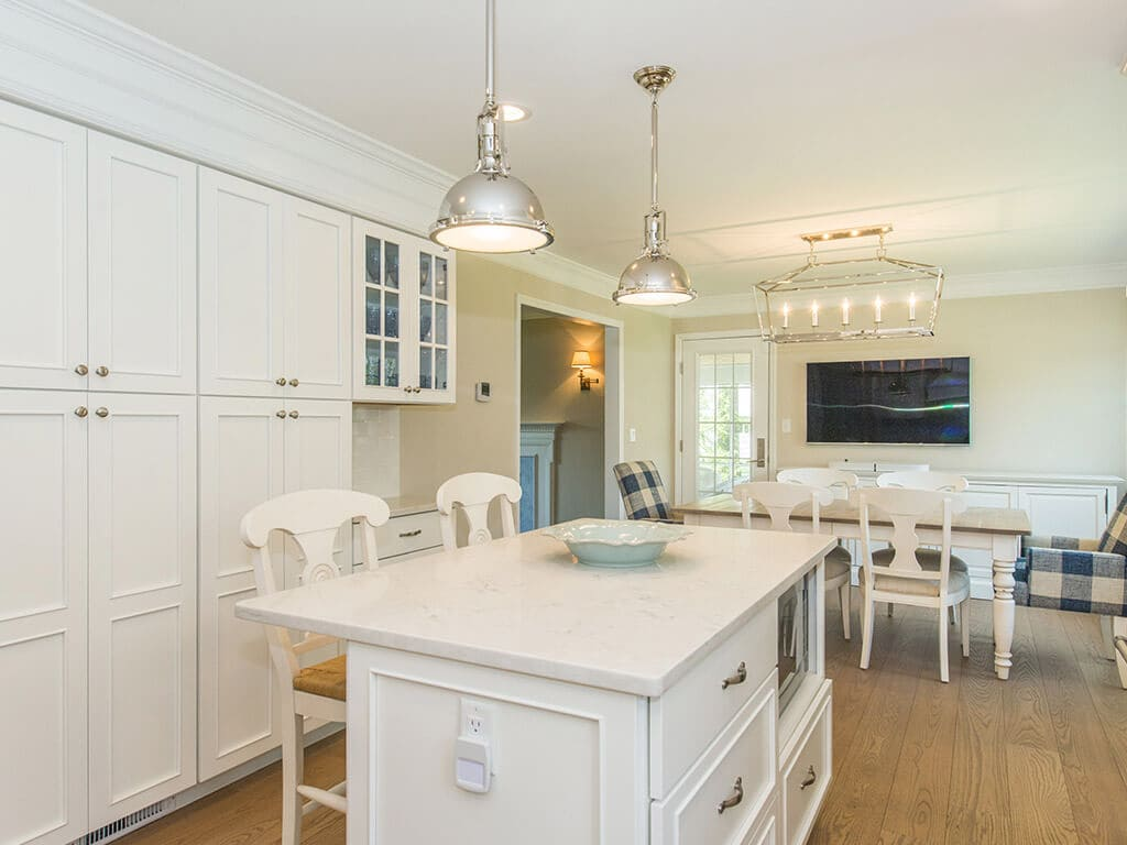 Open concept white kitchen remodel with white cabinets,  quartz countertops, crown molding, pendant lighting over island, wall removed for dining area and hardwood flooring in Morristown, NJ renovated by JMC Home Improvement Specialists