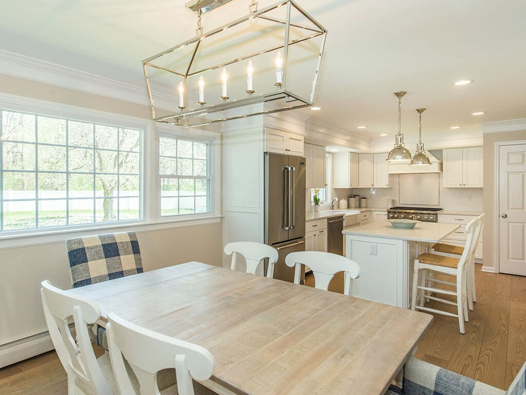 Open concept white kitchen remodel with white cabinets, quartz countertops, crown molding, pendant lighting over island, stainless appliances, wood hood and hardwood flooring in Morristown, NJ renovated by JMC Home Improvement Specialists