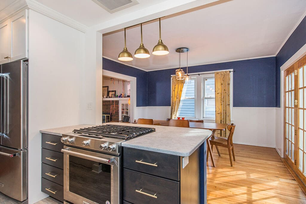 Open concept black and white kitchen remodel with white upper cabinets, black lower cabinets, white subway tile backsplash,  seating at peninsula with quartz counters, wall removed with exposed beam in Montclair, NJ renovated by JMC Home Improvement Specialists