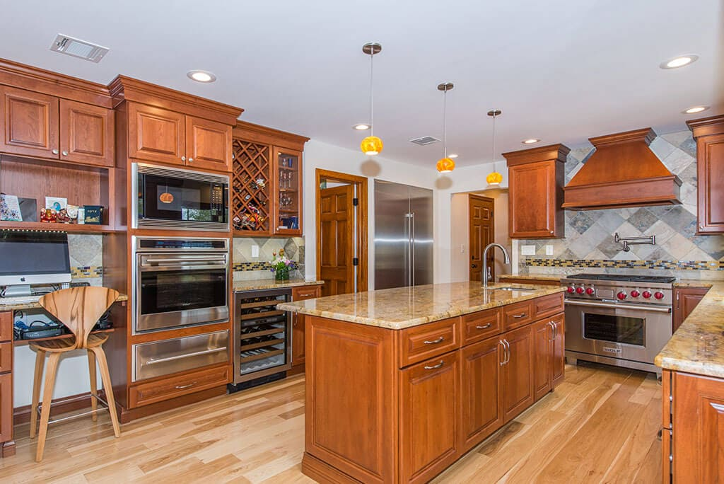 Wood cabinetry in kitchen remodel with freestanding wood hood, granite counters, built in ovens, wine fridge, desk area, build in shelving, crown molding, pendants over island, pot filler with mosaic backsplash in Morristown, NJ remodeled by JMC Home Improvement Specialists
