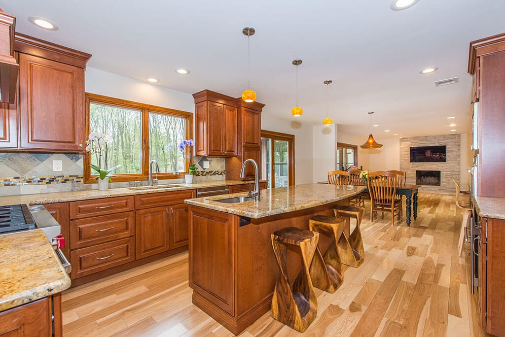 Open concept kitchen with wood cabinetry, granite counters with bar stools, crown molding, pendants over island, mosaic backsplash, undermount and bar sink, dining area with hardwood flooring throughout in Morristown, NJ remodeled by JMC Home Improvement Specialists
