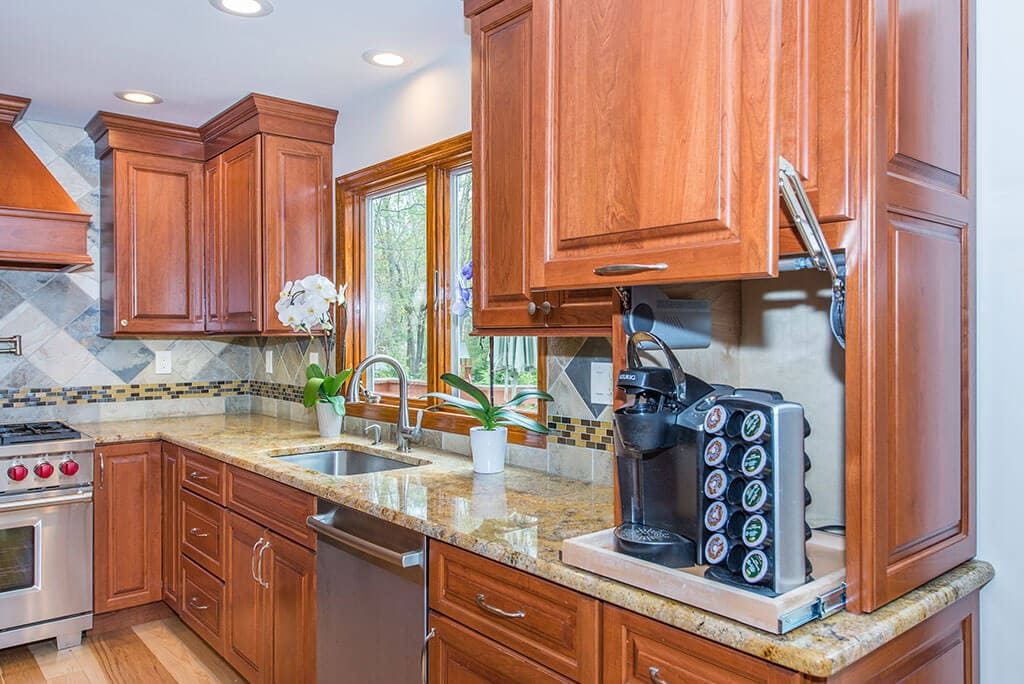 Wood cabinetry in kitchen remodel with hidden coffee station, granite counters, mosaic tile backsplash in Morristown, NJ renovated by JMC Home Improvement Specialists