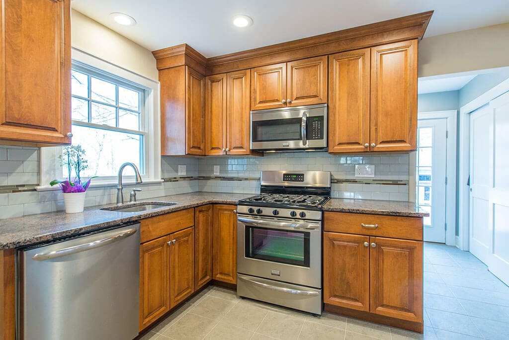 Kitchen remodel with raised panel wood cabinets, tile floor, subway tile backsplash with mosaic glass strip with undermount sink in Morristown, NJ remodeled by JMC Home Improvement Specialists