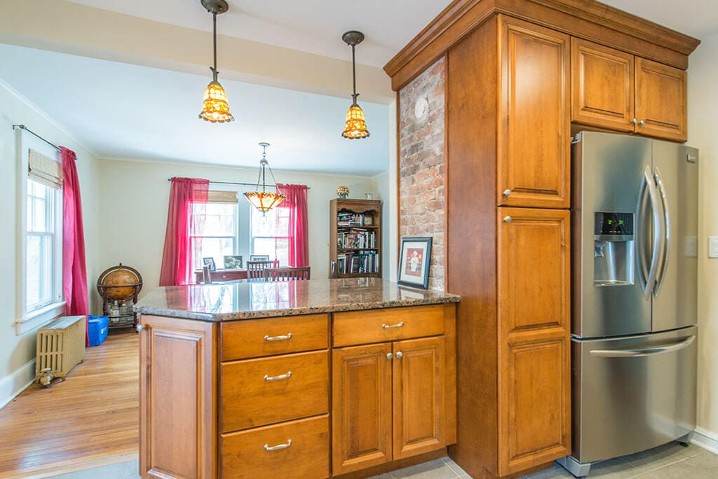 Open kitchen remodel with raised panel wood cabinets and pantry, with exposed brick at granite peninsula island with stainless steel appliances in Morristown, NJ remodeled by JMC Home Improvement Specialists
