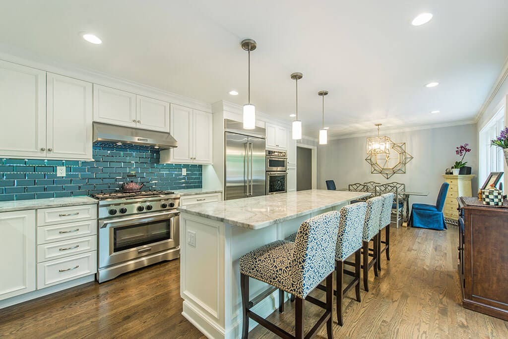 Open floor plan white kitchen with bevel edge glass tile backsplash, extended kitchen island for seating, granite counters, hardwood floor throughout in Morristown, NJ renovated by JMC Home Improvement Specialists