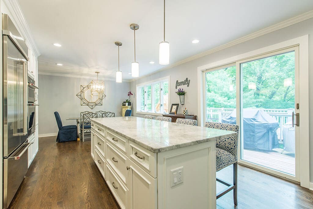 Open concept white kitchen remodel extended kitchen island for seating, granite counters, pendant lights above island and LED highhats, hardwood flooring in Morristown, NJ renovated by JMC Home Improvement Specialists