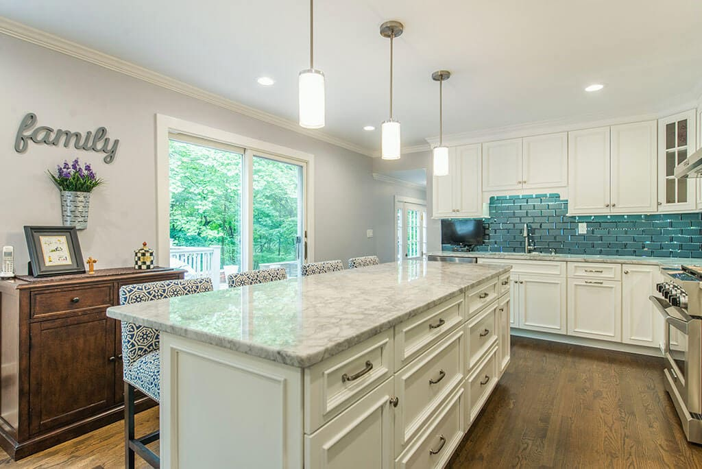 White eat-in kitchen remodel with beveled edge glass tile backsplash, granite counters, pendant lights above island and LED highhats, sliding door to deck, hardwood flooring in Morristown, NJ renovated by JMC Home Improvement Specialists