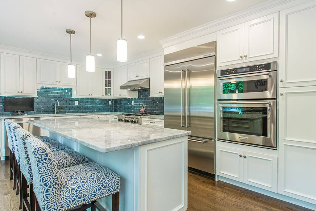 Kitchen remodel with white kitchen cabinets, with beveled edge glass tile backsplash, granite counters, pendant lights above island and LED highhats, metal hood, double oven in Morristown, New Jersey renovated by JMC Home Improvement Specialists