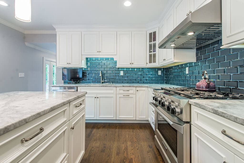 Open kitchen remodel with white kitchen cabinets, with beveled edge glass tile backsplash, granite counters, pendant lights above island and LED highhats, metal hood, double oven in Morris County, New Jersey renovated by JMC Home Improvement Specialists