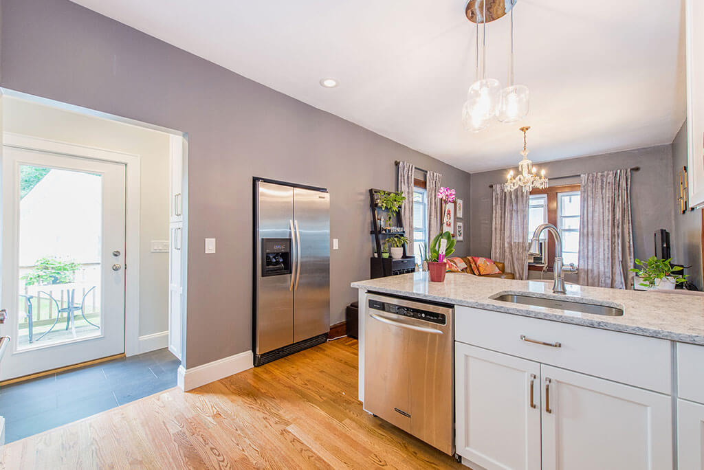 Small white contemporary open concept kitchen remodel with granite countertop, pendant lighting above peninsula, in wall refrigerator with hardwood flooring in Essex, NJ remodeled by JMC Home Improvement Specialists