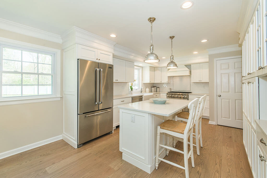 Open concept white kitchen with white shaker cabinets, quartz countertops and eat in island with hardwood flooring in Morristown, NJ remodeled by JMC Home Improvement Specialists
