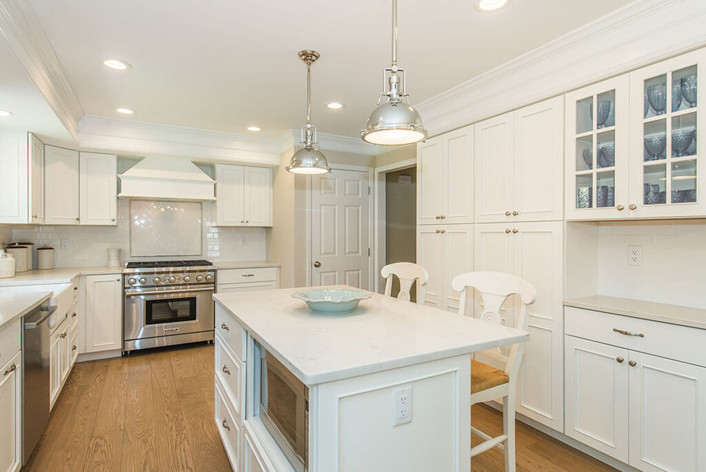 White kitchen remodel with white shaker cabinets, glass upper cabinets, quartz countertops with microwave shelf in eat in island with hardwood flooring in Morristown, NJ remodeled by JMC Home Improvement Specialists