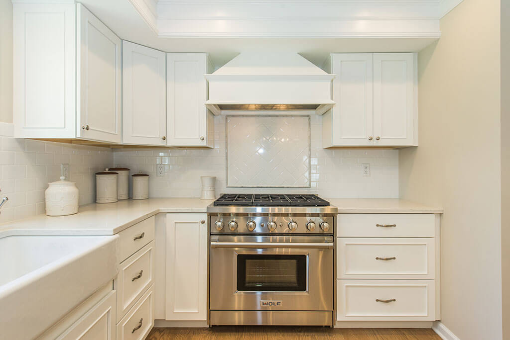 White kitchen remodel with white shaker cabinets, custom wood hood, white apron sink in Morristown, NJ remodeled by JMC Home Improvement Specialists