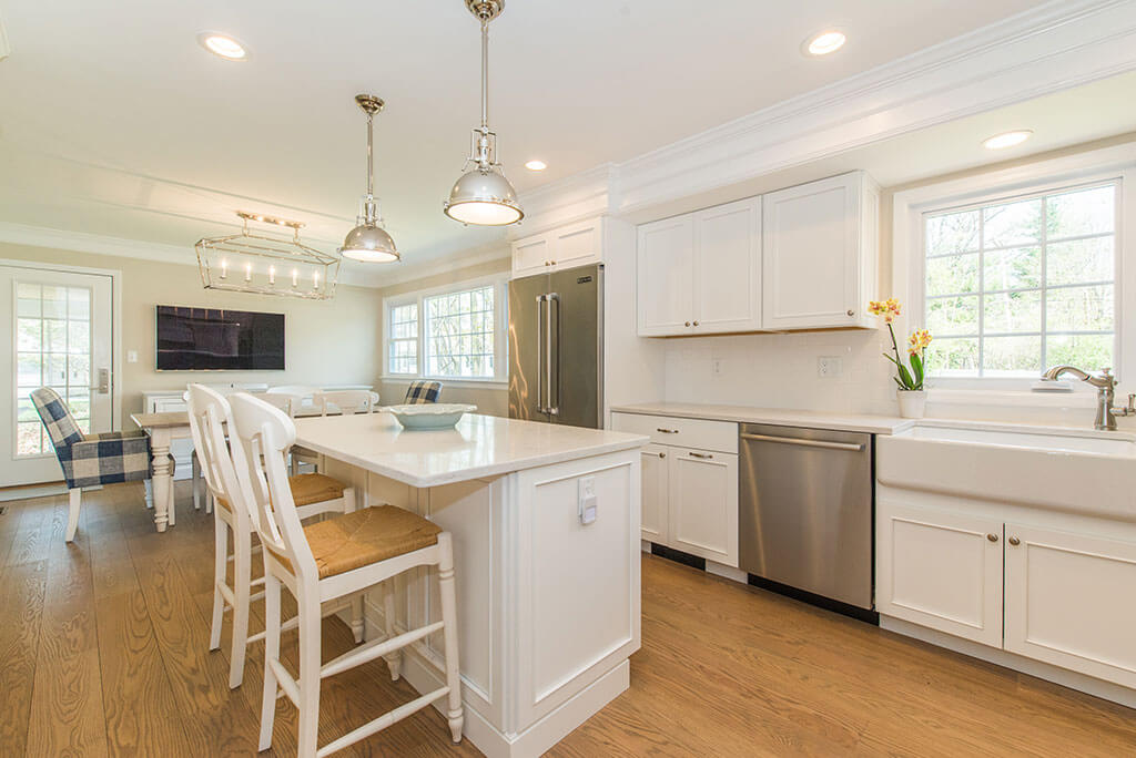 Open concept white kitchen remodel with white shaker cabinets, white apron sink, quartz countertop with hardwood flooring in Morristown, NJ remodeled by JMC Home Improvement Specialists