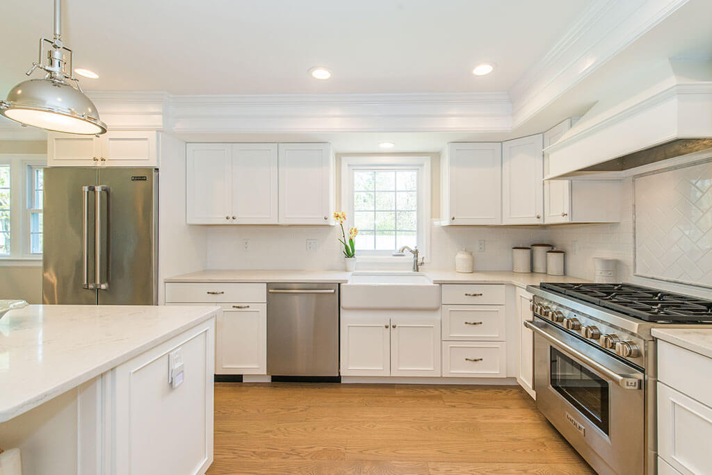 White open concept kitchen remodel with white shaker cabinets, white apron sink, quartz countertop, wood hood above stove with hardwood flooring in Morris County, NJ remodeled by JMC Home Improvement Specialists