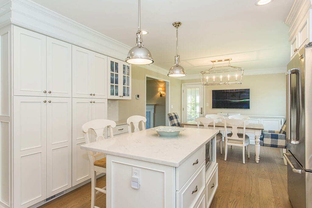 White open concept eat in kitchen remodel with white shaker cabinets, pantry cabinets, quartz countertop, pendant and highhat LED lighting with hardwood flooring in Morris County, NJ remodeled by JMC Home Improvement Specialists