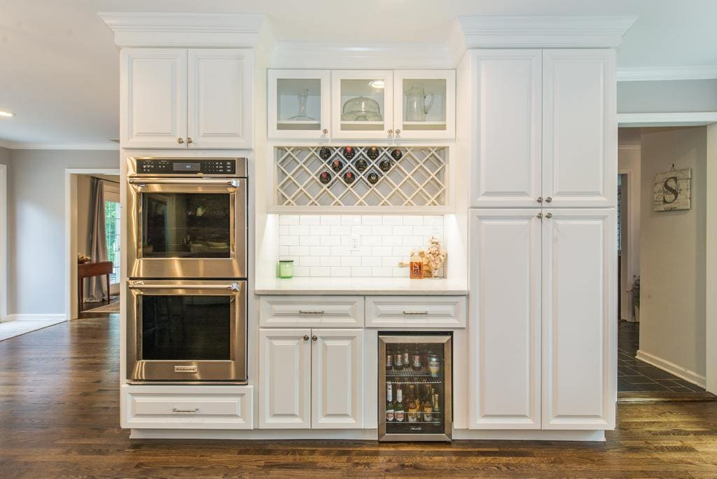 Double oven, glass cabinet doors above wine rack, bar fridge, subway tile backsplash, white cabinets with undercabinet lighting, tall pantry cabinets with hardwood flooring in Denville, NJ remodeled by JMC Home Improvement Specialists