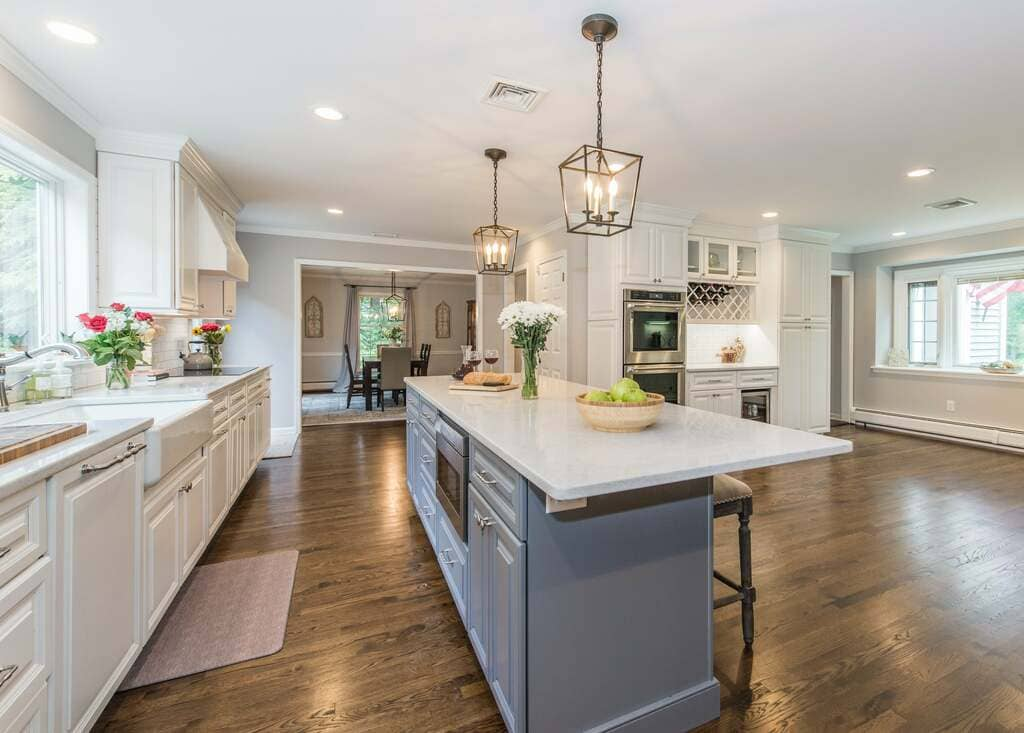 Grey and white two tone open concept kitchen with grey island with quartz counter, white apron sink, wood hood over cooktop, undercabinet lighting, hidden dishwasher and hardwood flooring in Denville, NJ remodeled by JMC Home Improvement Specialists