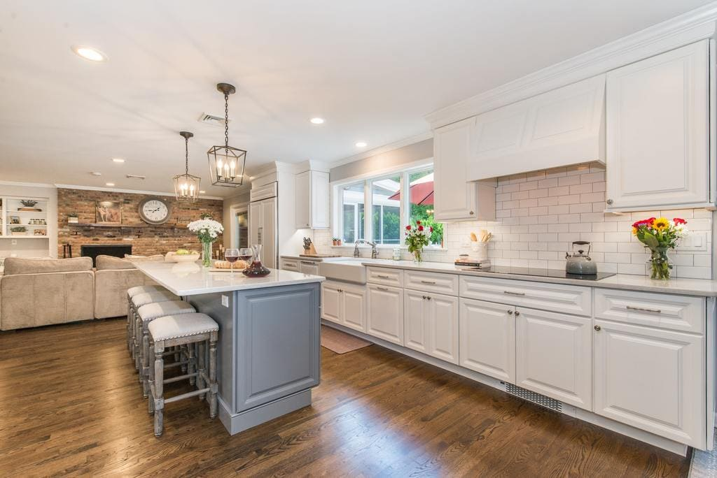 Open concept Grey and white kitchen remodel with grey island with quartz counter, white apron sink, wood hood over cooktop, undercabinet lighting, subway tile backsplash, exposed brick in family room in Denville, NJ remodeled by JMC Home Improvement Specialists
