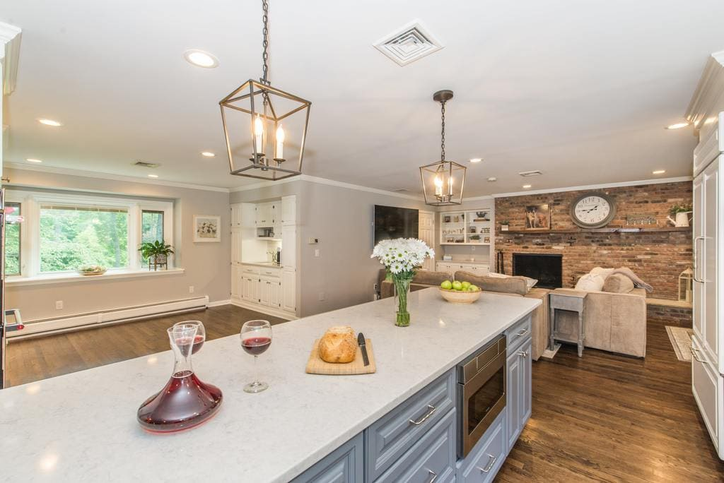 Open concept grey and white kitchen remodel with grey island with quartz counter and microwave shelf, paneled fridge, exposed brick in family room in Denville, NJ remodeled by JMC Home Improvement Specialists