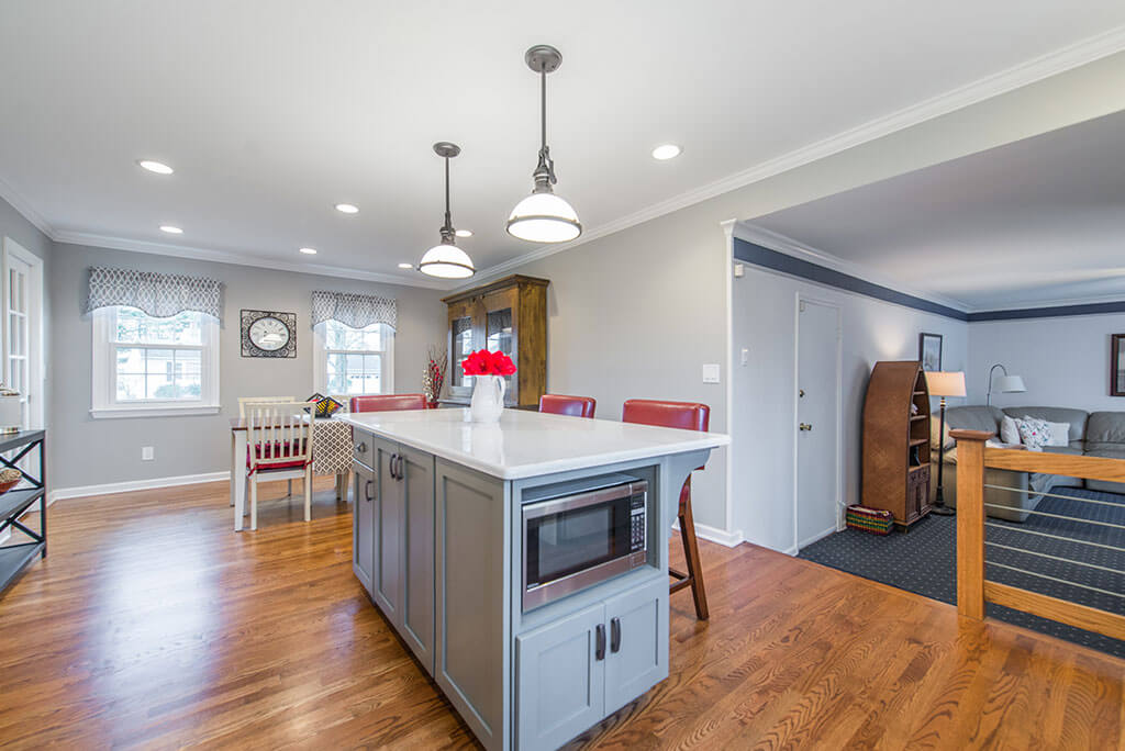 White and Grey two tone eat in kitchen remodel with hardwood flooring, quartz counters, pendant lighting over island, microwave shelf in island, LED highhats in Parsippany, NJ remodeled by JMC Home Improvement Specialists