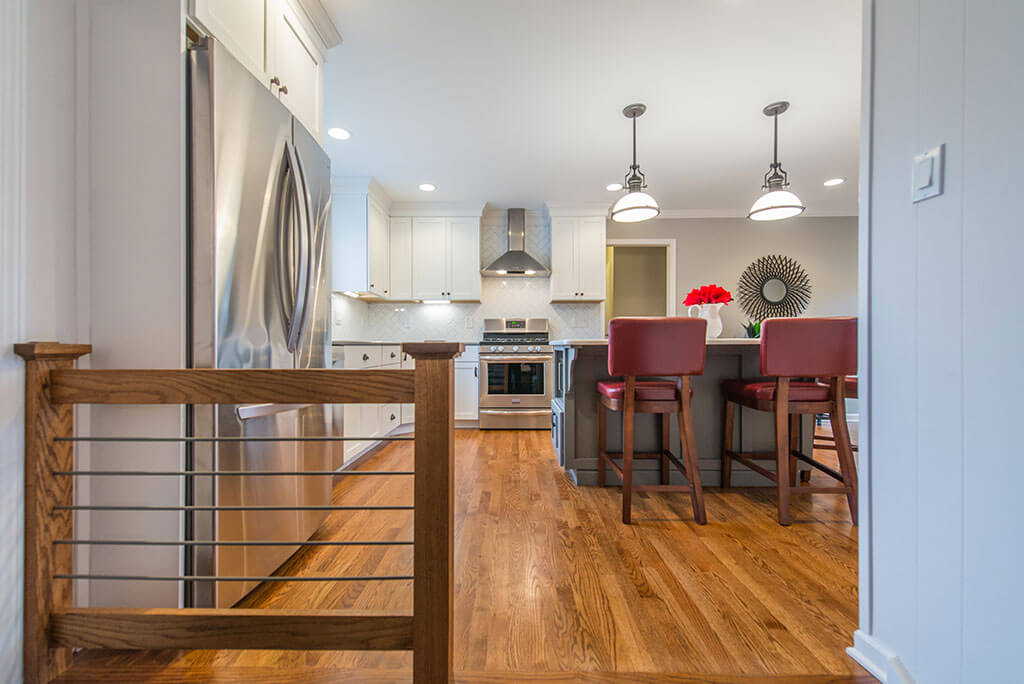 Eat in two tone open concept kitchen remodel with hardwood flooring, white shaker cabinets, quartz counters, pendant lighting over island, metal railing, freestanding hood and LED highhats in Parsippany, NJ remodeled by JMC Home Improvement Specialists