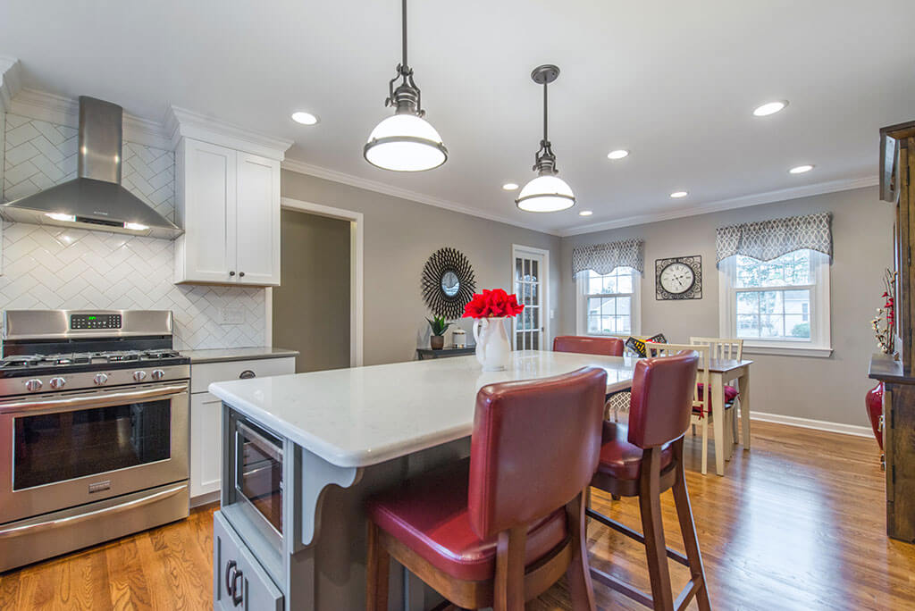 Eat in two tone open concept kitchen remodel with herringbone white backsplash, freestanding hood, white shaker cabinets, quartz counters, pendant lighting over island and LED highhats, grey and white cabinets with red accents in Parsippany, NJ remodeled by JMC Home Improvement Specialists