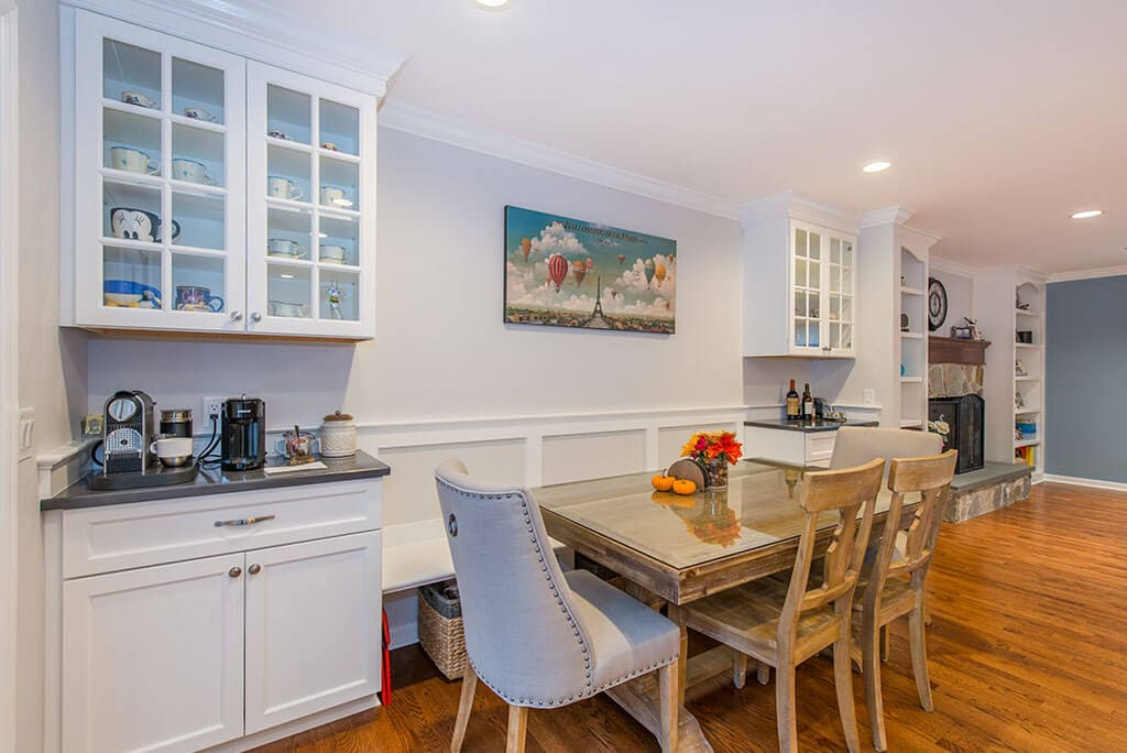 Kitchen remodel with table for dining, coffee station with white shaker lower cabinets and glass upper cabinets in Randolph, NJ remodeled by JMC Home Improvement Specialists