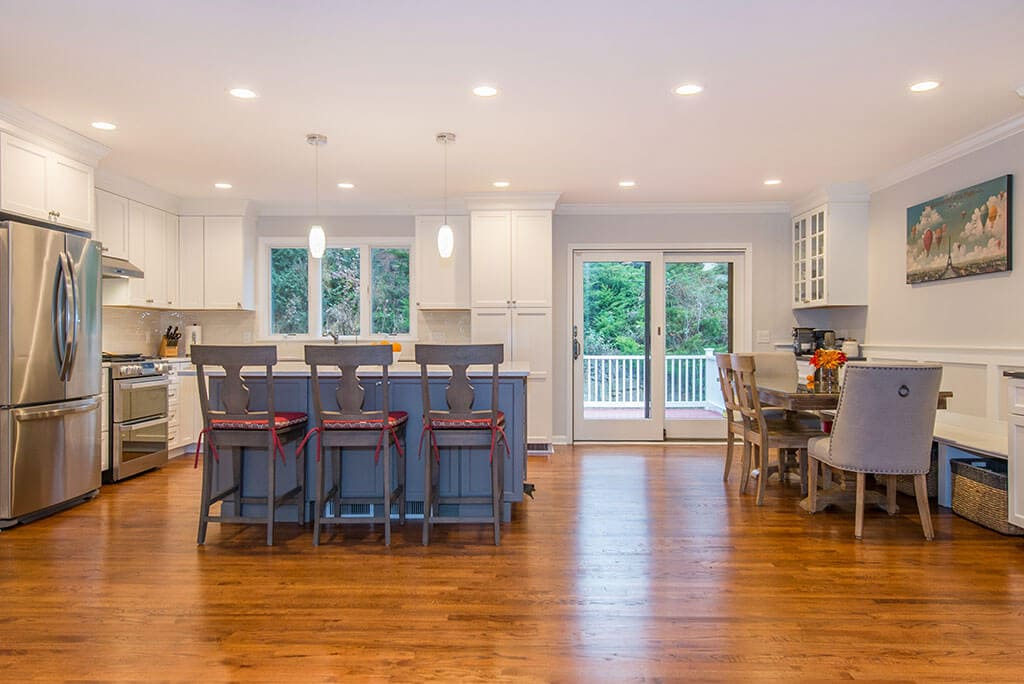 Open floor plan kitchen with flush header, hardwood flooring, sliding door, white shaker cabinets, eat-in kitchen island with pendant and LED highhat lighting in Randolph, NJ remodeled by JMC Home Improvement Specialists