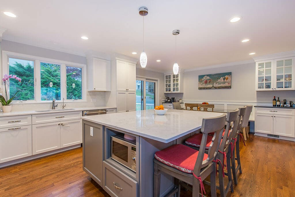 White kitchen remodel with hardwood flooring, triple window above sink, microwave shelf in eat in grey island with pendant lighting in Randolph, NJ remodeled by JMC Home Improvement Specialists