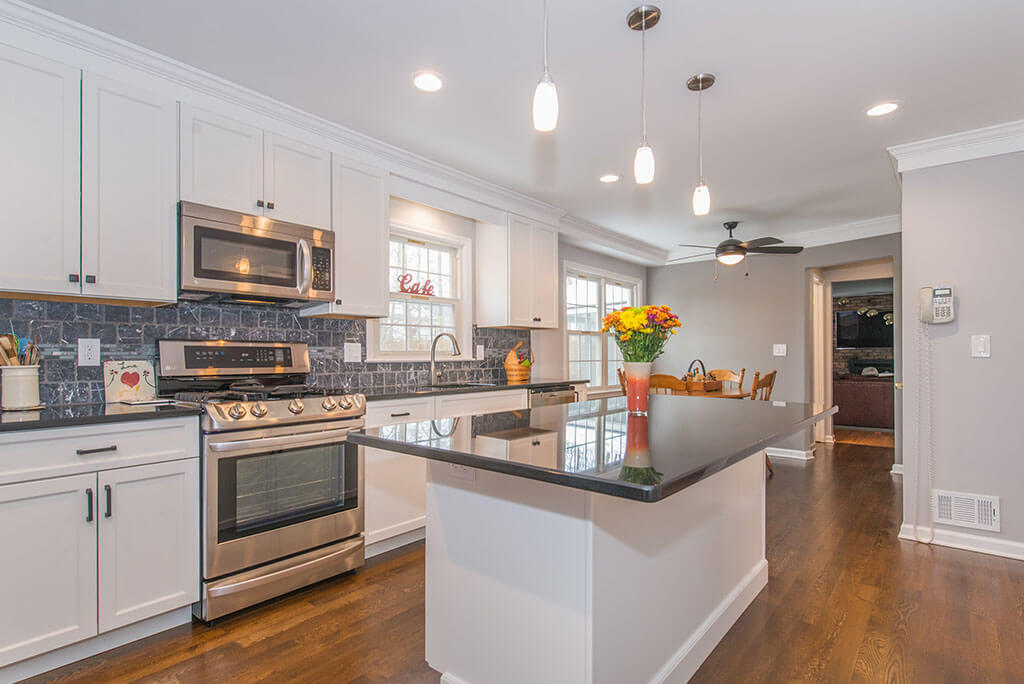 White eat in kitchen remodel with hardwood flooring, granite counters, pendant lighting, marble backsplash, stainless appliances in Randolph, NJ remodeled by JMC Home Improvement Specialists]['