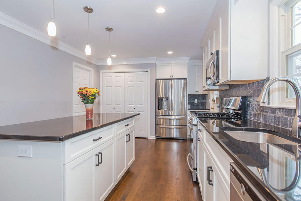 White kitchen remodel with hardwood flooring, granite counters, pendant lighting, marble backsplash, stainless appliances and undermount sink in Randolph, NJ remodeled by JMC Home Improvement Specialists