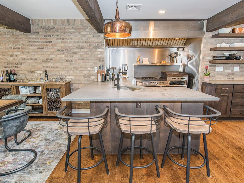 Open concept industrial kitchen with exposed brick wall concrete countertop in Rockaway, NJ remodeled by JMC Home Improvement Specialists