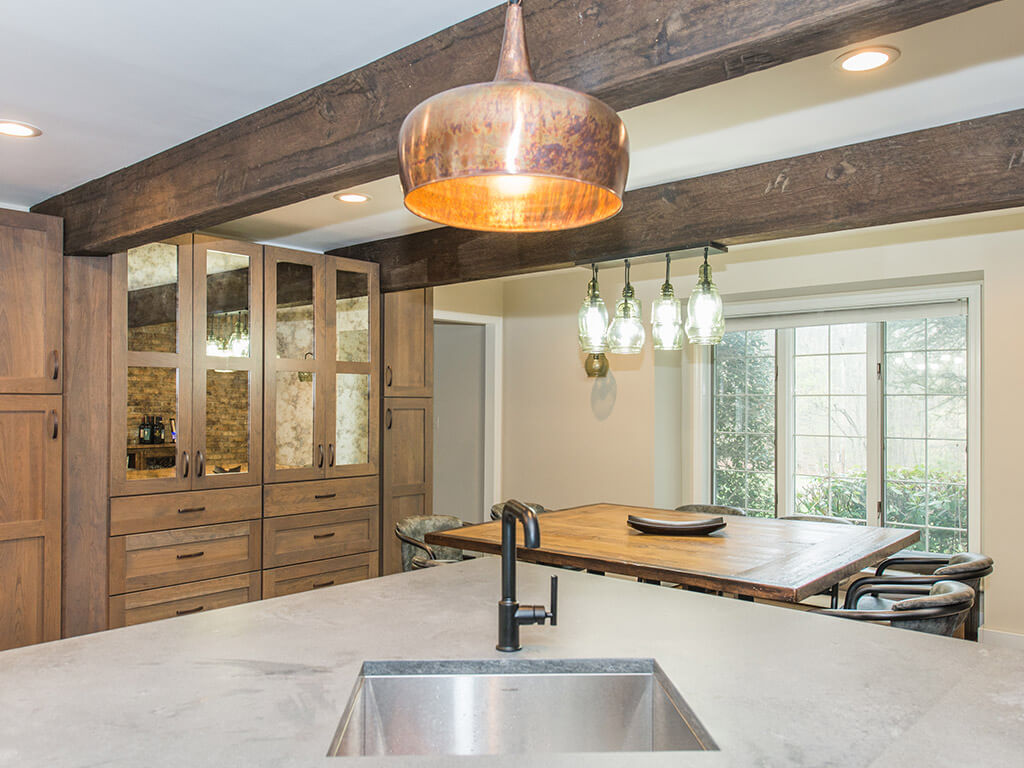 Rustic Open floor plan industrial kitchen, wood shaker cabinets with mirror doors, wood beams, concrete countertop with bar sink in Rockaway, NJ remodeled by JMC Home Improvement Specialists