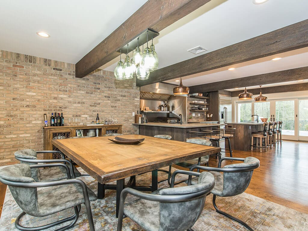 Eat in rustic open floor plan kitchen with exposed brick, industrial  range and hood, wood beams and hardwood flooring throughout in Rockaway, NJ remodeled by JMC Home Improvement Specialists