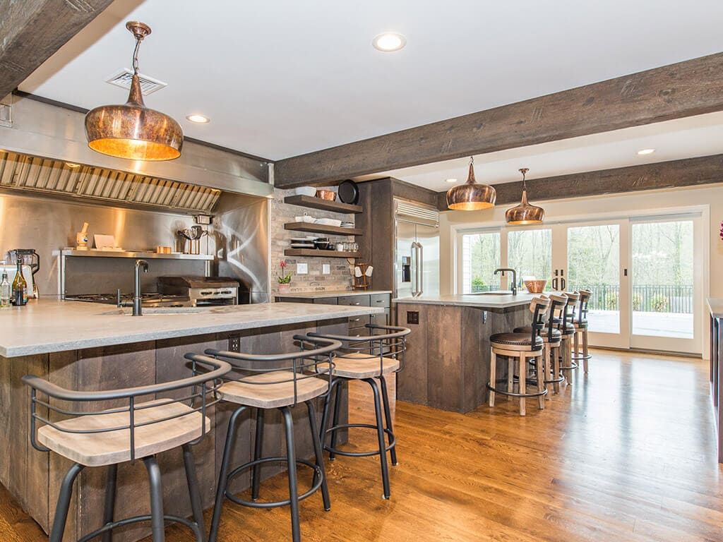 Rustic open floor plan kitchen with concrete island and peninsula, industrial  range and hood, wood beams and hardwood flooring throughout in Rockaway, NJ remodeled by JMC Home Improvement Specialists