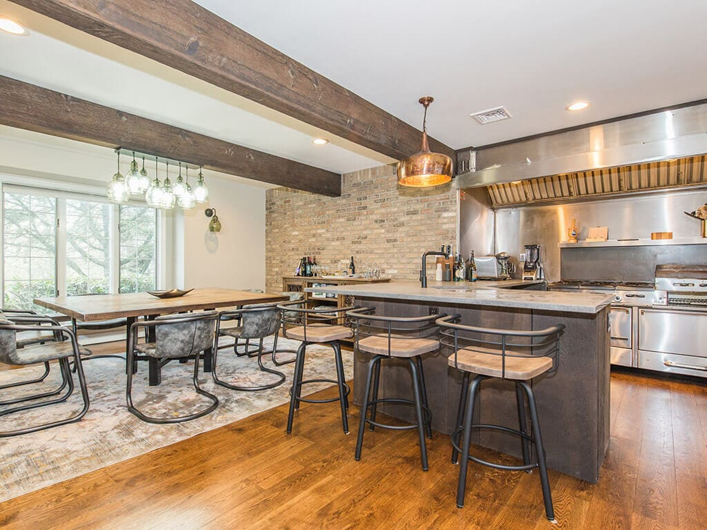 Rustic open floor plan kitchen with exposed brick, concrete peninsula, industrial  range and hood, wood beams and hardwood flooring throughout in Rockaway, NJ remodeled by JMC Home Improvement Specialists